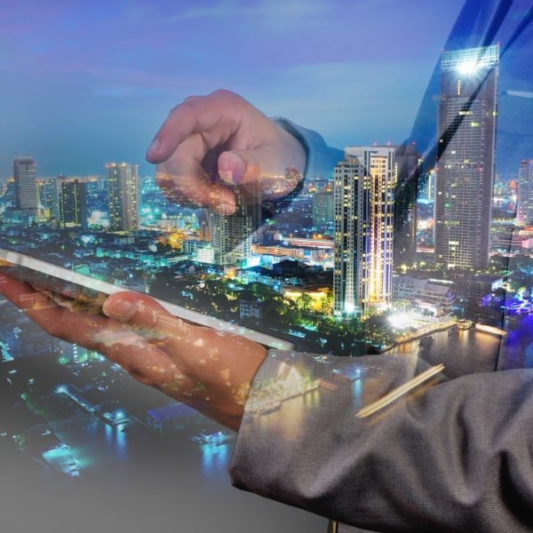 Double Exposure image of Businessman from Industry use Digital Tablet and City