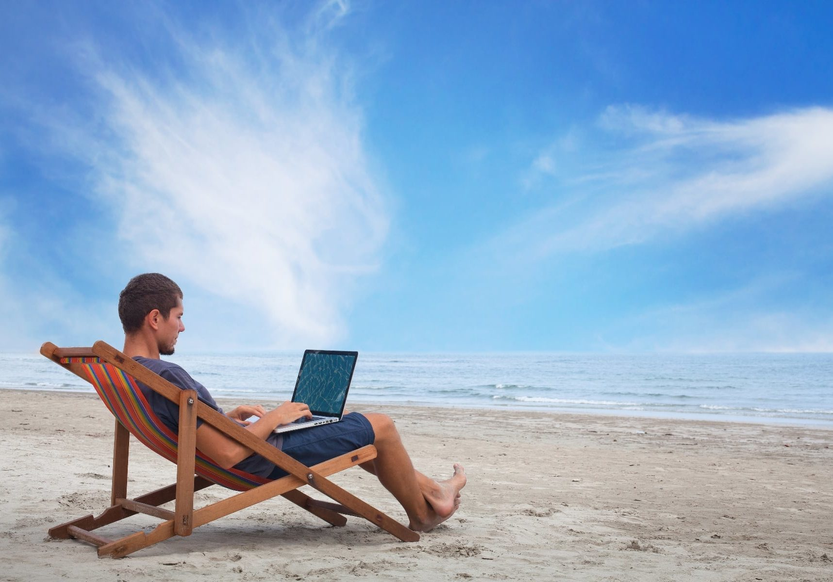 businessman remote working with computer on the beach